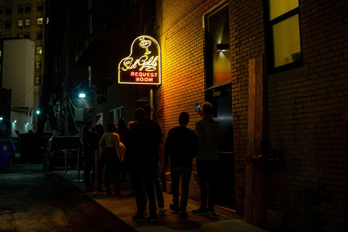 People gather near the alley sign for Sid Gold's Request Room in downtown Detroit on an evening.