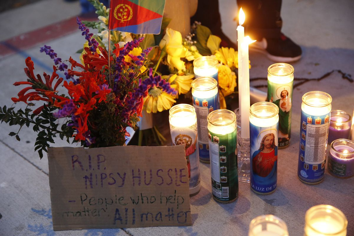 A sign for rapper Nipsey Hussle is left by candles set up across from a clothing store owned by Hussle in Los Angeles, Sunday, March 31, 2019. Hussle, the skilled and respected West Coast rapper who had a decade-long success with mixtapes but hit new heig