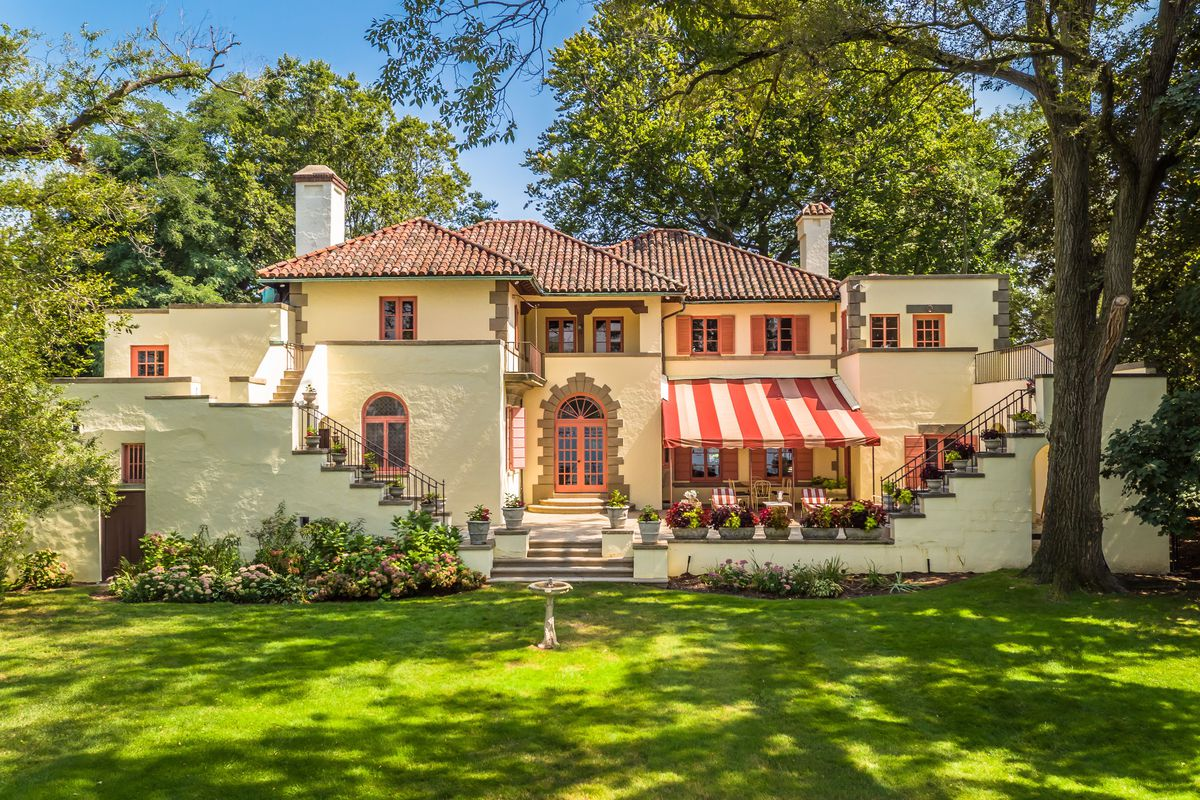 Spanish-style home with tiled roof, balconies, awnings, and steps on either side with lawn.