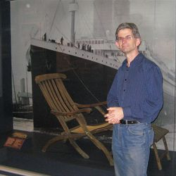 In this Feb. 28, 2012 photo, Gerry Lunn, curator of the Maritime Museum of the Atlantic in Halifax, Nova Scotia, Canada, stands next to a Titanic deck chair given to the minister who performed services on one of the ships that recovered bodies. Lunn said the city was in mourning for months after the disaster. One hundred years ago, ships from this old port city on the Atlantic set out to recover the Titanic's dead. They brought back more than 330 bodies; 150 are buried in three Halifax cemeteries. (AP Photo/Robert Gillies)