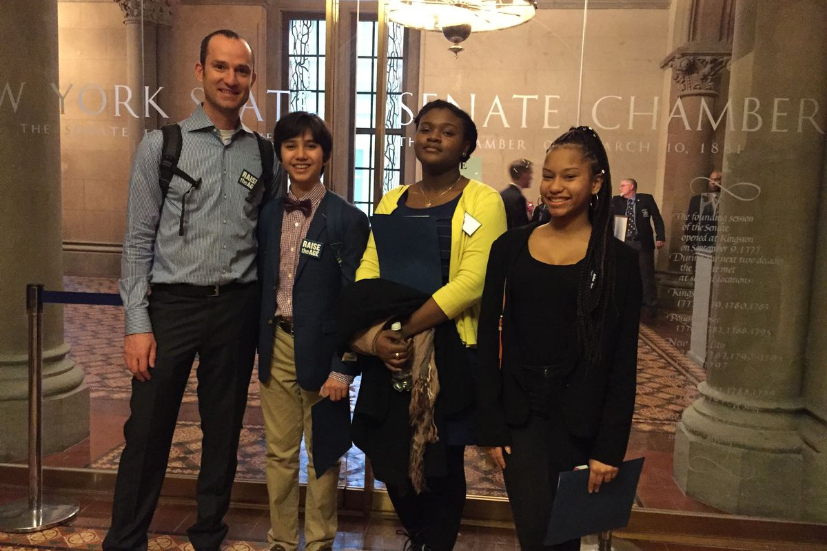 Assistant Principal Benjamin Geballe (left) poses outside the New York Senate chamber with students Dash Avincula (center left), Alex Bristol (center right) and Kayla Mowatt (right).