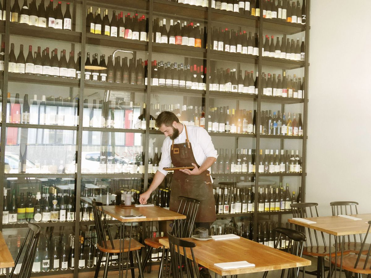 A waiter sets the places at a two-top in a bright dining room with large, glass-enclosed shelves of wine bottles reaching to the ceiling behind him near the tables.