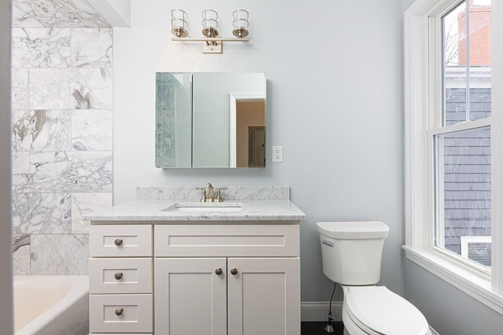A small bathroom with a counter around the sink.