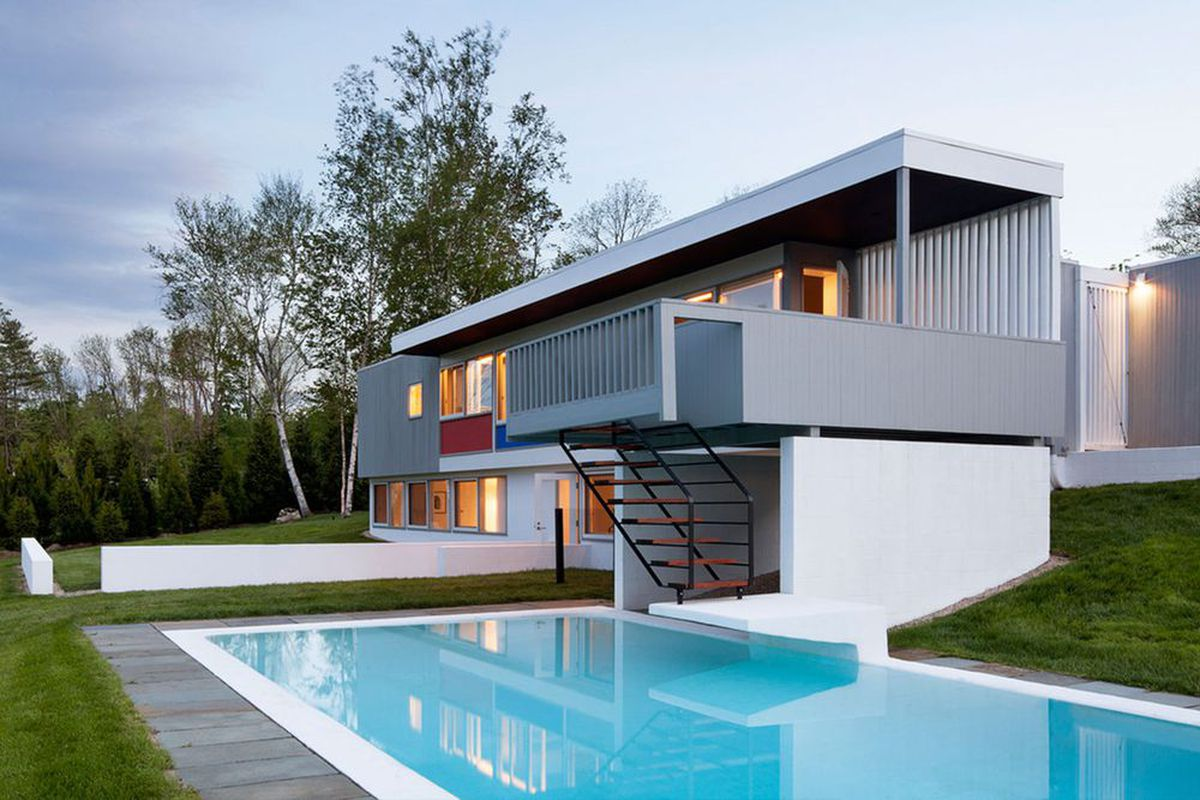 Shot of block modern house with overhanging porch and a pool set on a grassy, sloping site.