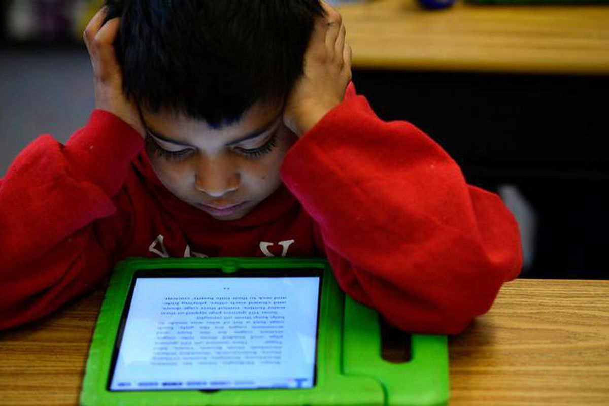 Justin Machado, 9, reads on his iPad during his 3rd grade class  at Ashley Elementary in 2015.