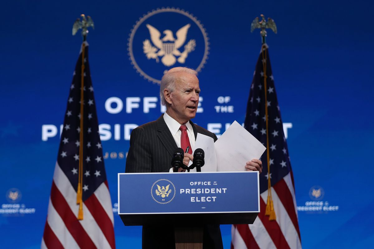 Joe Biden standing onstage behind a podium that has two flags flanking him.