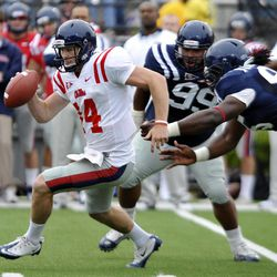Mississippi quarterback Bo Wallace (14) is chased by Gilbert Pena (99) and Bryon Bennett (95) during their annual spring NCAA college football game in Oxford, Miss. on Saturday, April 21, 2012.