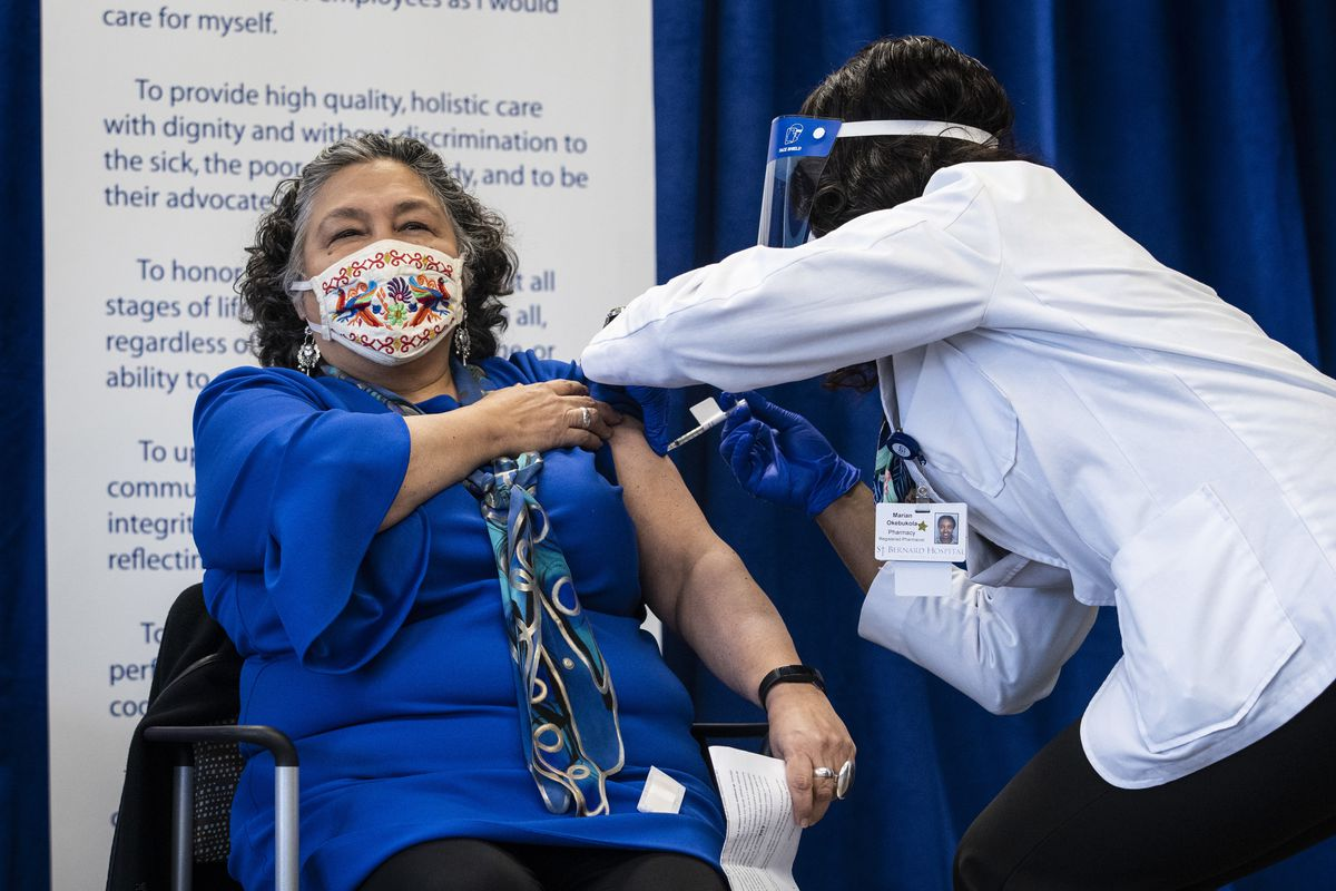 Sylvia Puente, president of the Latino Policy Forum, receives her first dose of the Pfizer-BioNTech COVID-19 vaccine Monday at St. Bernard Hospital on the South Side.