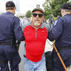 A demonstrator known only as the Captain is detained by police during an unscheduled protest march,Tuesday, Sept. 4, 2012, in Charlotte, N.C.