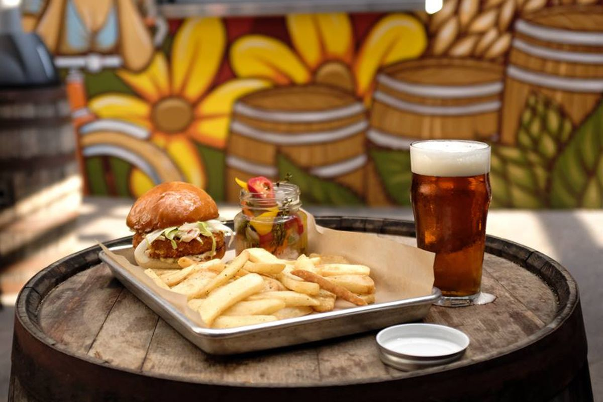 A silver sheet tray with a sandwich and French fries, plus a beer, in front of the Adam Turman mural at the old Butcher & the Boar