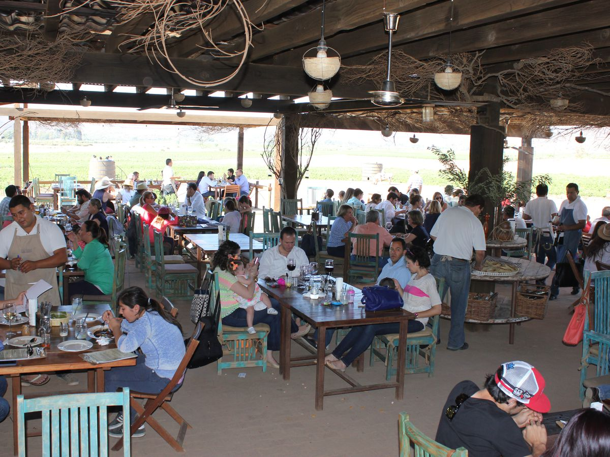 Diners fill wooden tables as servers move about in an outdoor, covered dining area on a dirt floor