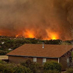 The Yarnell Hill Fire burns through the town of Yarnell, Ariz. on Sunday, June 30, 2013. The fire started Friday and picked up momentum as the area experienced high temperatures, low humidity and windy conditions. It has forced the evacuation of residents in the Peeples Valley area and in the town of Yarnell. (AP Photo/The Arizona Republic, Tom Story)