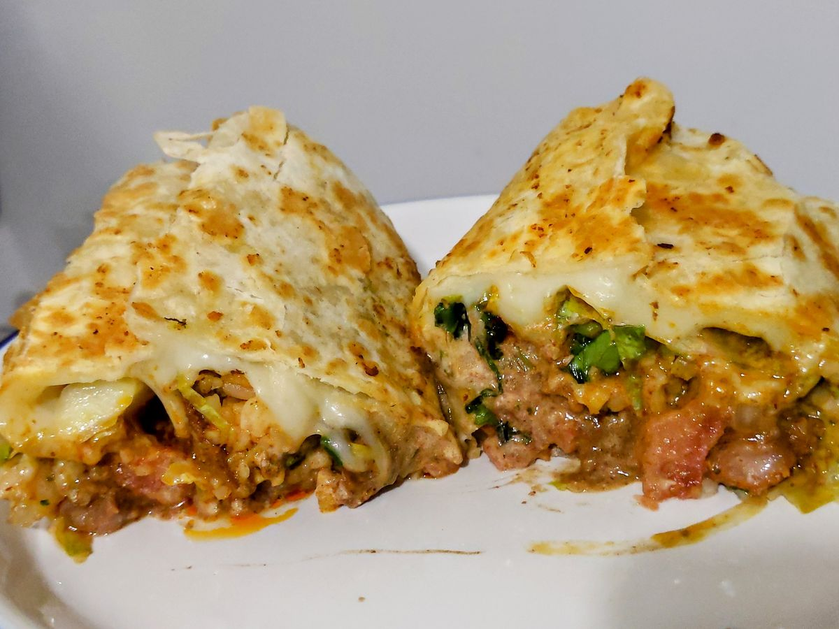 A burrito browned on the outside cut in half and oozing cheese and meat.