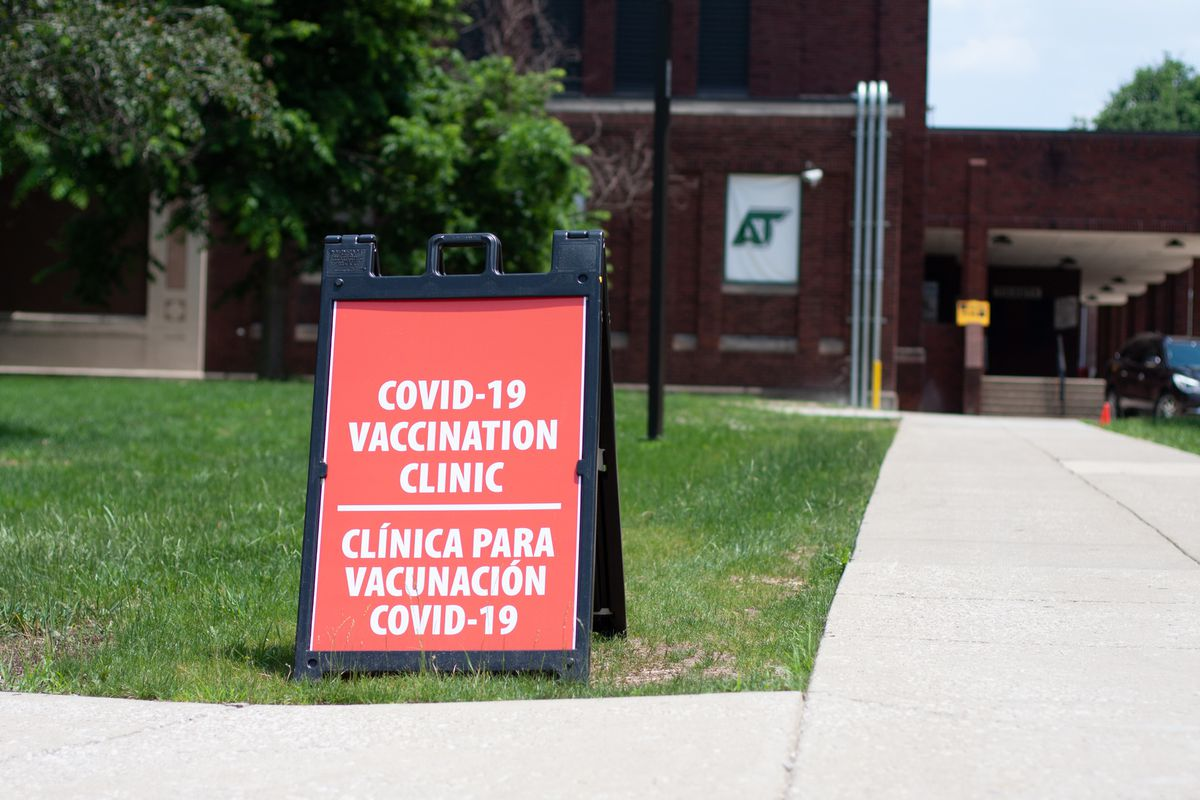 """A red clapboard sign sits on a patch of green grass in front of a red brick school building. The sign reads """"covid-19 vaccination clinic, clínica para vacunación de covid-19"""""""