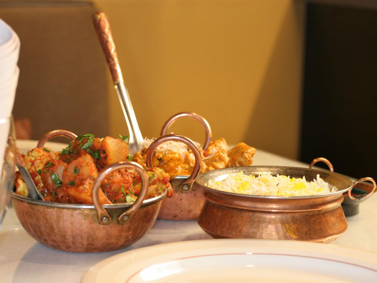 A view of three copper bowls filled with spiced potatoes and rice.