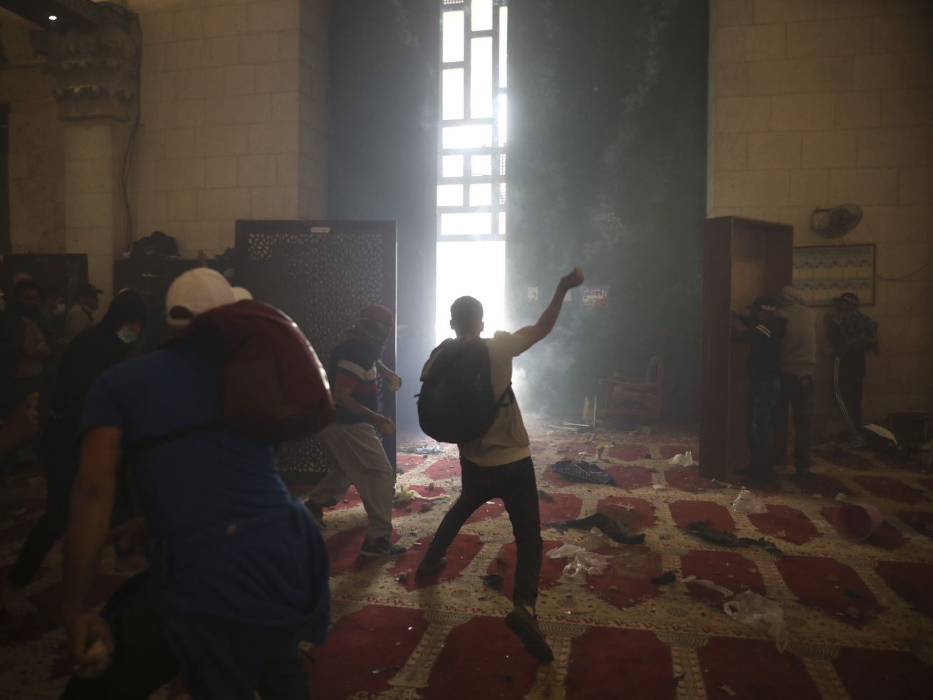 Palestinians inside the Al-Aqsa mosque clash with Israeli security forces at the Al Aqsa Mosque compound in Jerusalem's Old City Monday, May 10, 2021.