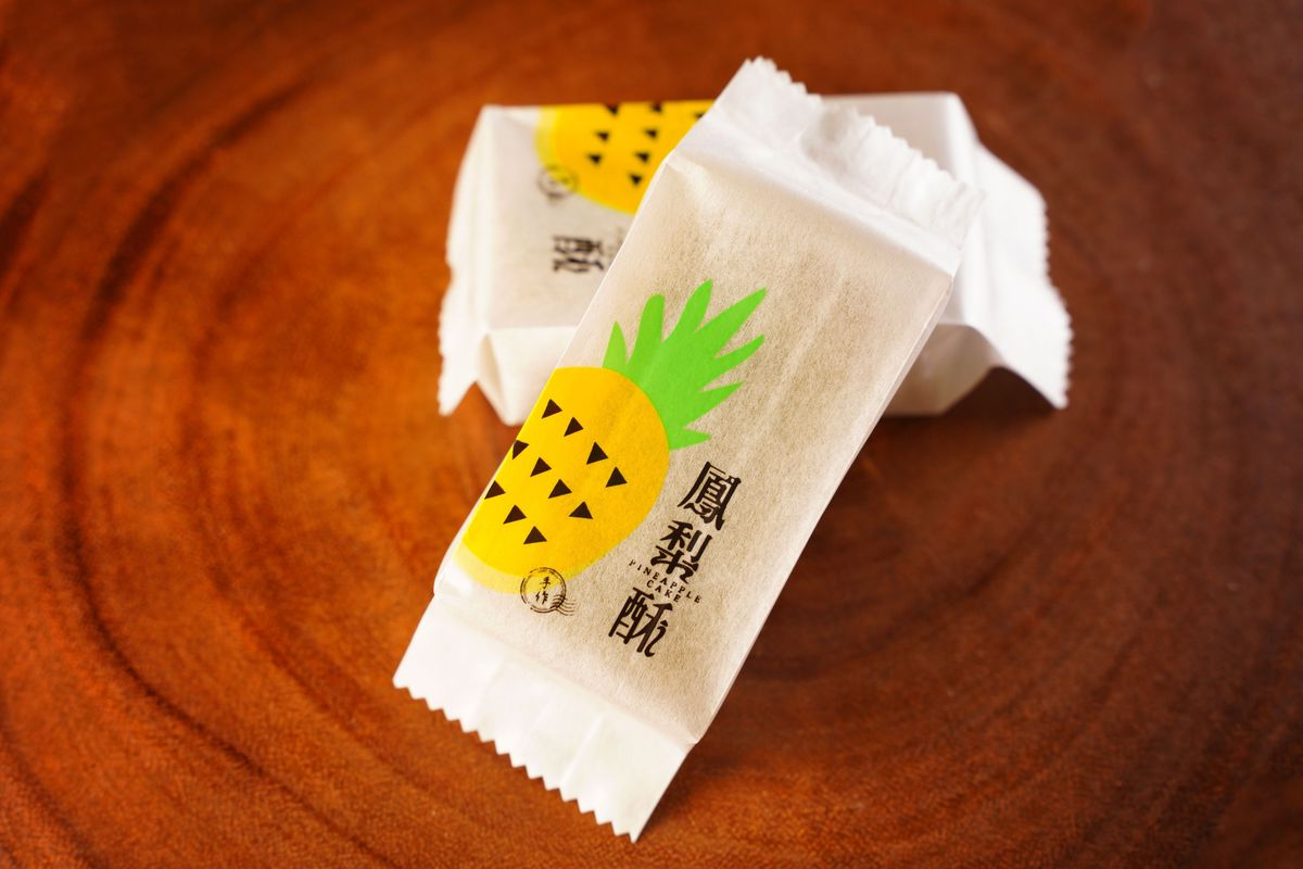 Two individually wrapped pineapple cakes, with a cute pineapple logo