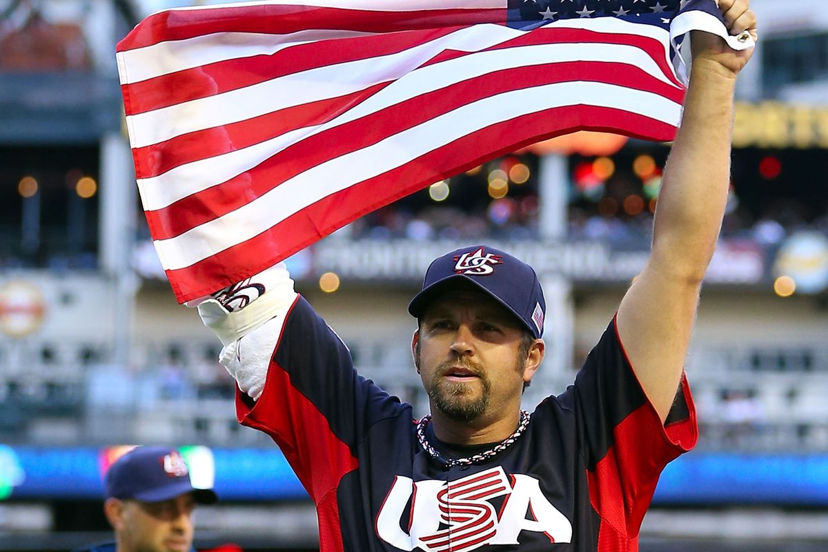 Heath Bell waves the USA flag after yesterday's victory over Canada.