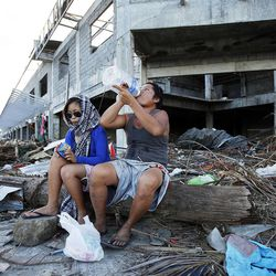 Noe Pica and his daughter Carell Pica sit in the rubble in Tacloban, Philippines, Tuesday, Nov. 19, 2013, after losing their home in a typhoon.