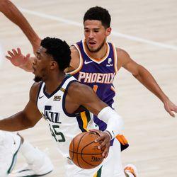 Utah Jazz guard Donovan Mitchell (45) dribbles against Phoenix Suns guard Devin Booker (1) during an NBA preseason game at Vivint Smart Home Arena in Salt Lake City on Saturday, Dec. 12, 2020.