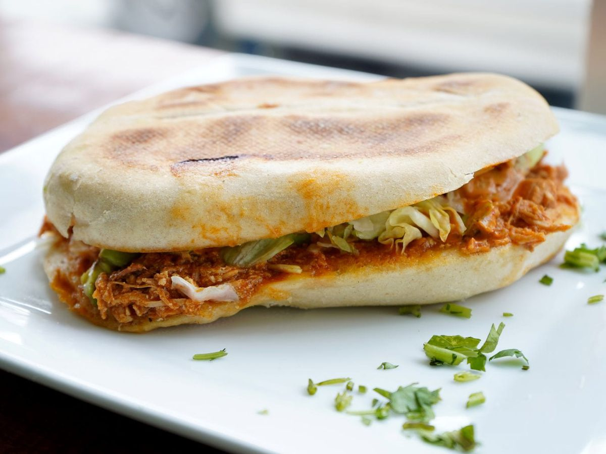 A Mexican torta sits on a white plate with green herbs scattered around it.