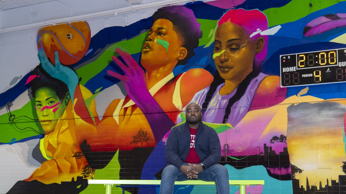 """Artist Max Sansing in front of his mural """"The City is Yours"""" that he painted in the gym at the Dr. Martin Luther King Jr. Boys & Girls Club at 2950 W. Washington Blvd. on the West Side."""