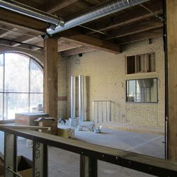 The upstairs dining area featuring exposed beams and floor to ceiling windows.