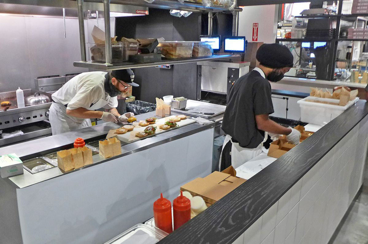 Two men put burgers together at two separate counters.