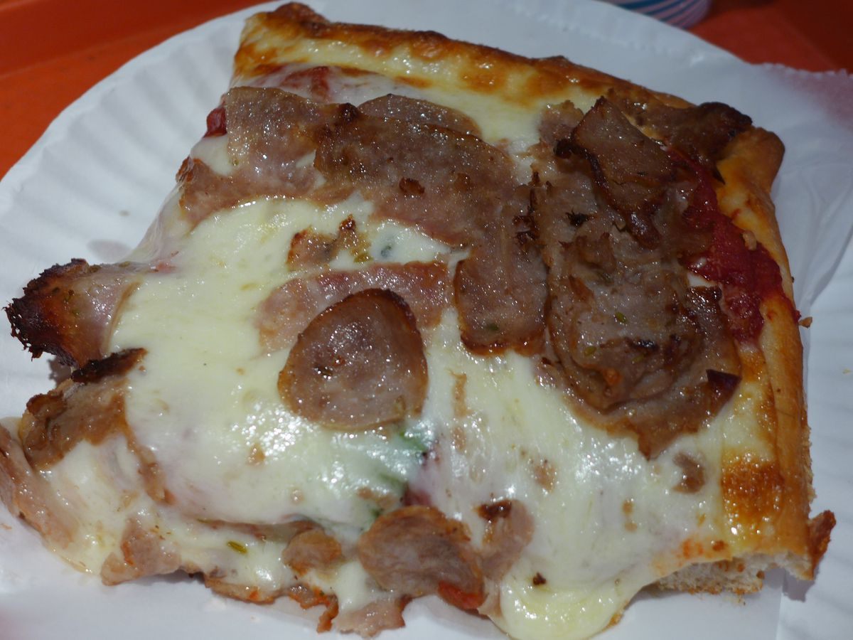 A very cheesy square slice with browned crust shining and lots of sliced Italian sausage.