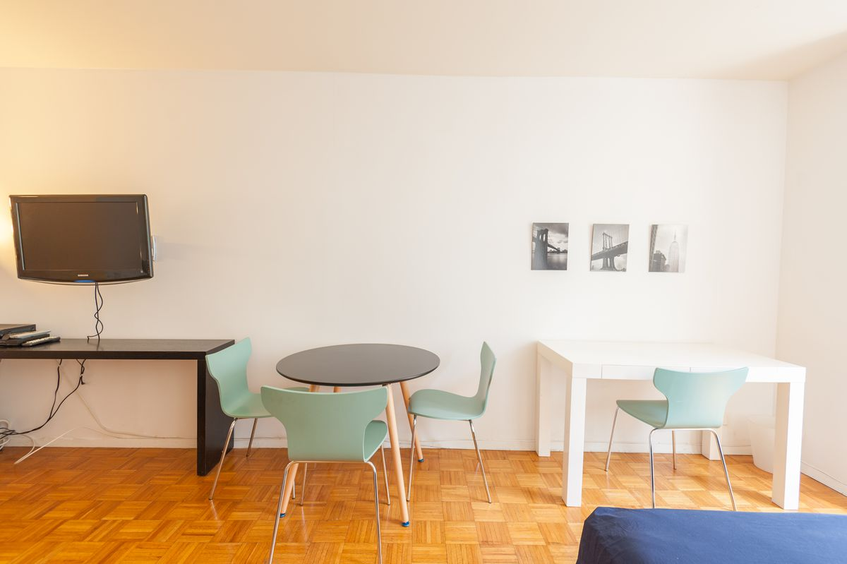 A room with a round dining table, three light green chairs, a TV, and a white desk.