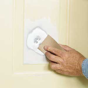<p>Sand the dented area down to bare metal with 150-grit sandpaper. Be sure to remove paint from deep crevices.</p>