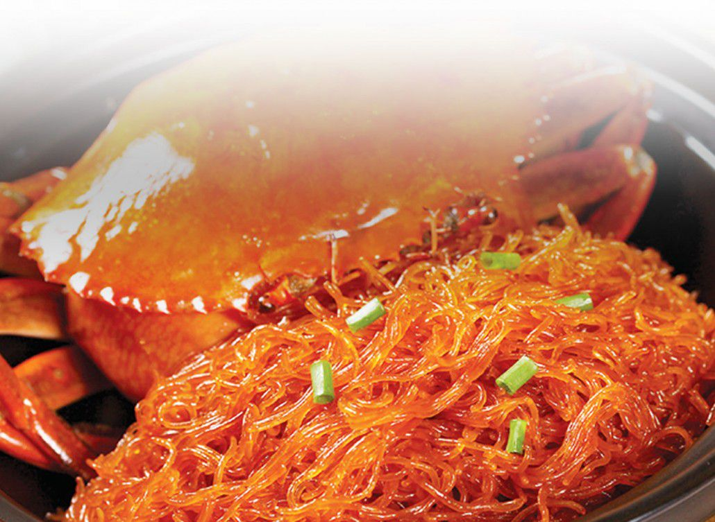 A closeup of glass noodles in a red sauce, with a giant crab in the background.