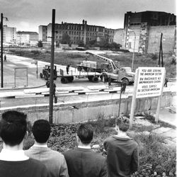 West Berliners, with their backs to camera, watch East Berliners unload prefabricated concrete plates to reinforce the Berlin Wall at Wilhelm St. in Berlin, Germany, on Sept. 12, 1961. The sector border is being reinforced with roadblocks on every street leading into West Berlin in order to prevent further escapes by trucks.