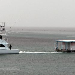 A houseboat is towed in the middle keys as the Florida Keys prepare for Tropical Storm Isaac, Saturday, Aug 25, 2012. Florida Gov. Rick Scott had declared a state of emergency and a hurricane warning has been issued for the Florida Keys, as officials warn tourists to leave. (AP Photo/The Miami Herald, Walter Michot)