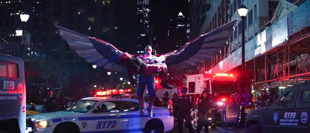 Sam, in the new Captain America wingsuit, lands with Karli in his arms