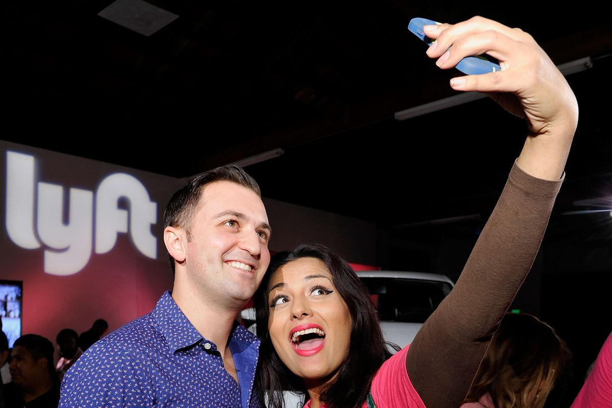 Lyft co-founder John Zimmer poses for a selfie with a Lyft driver