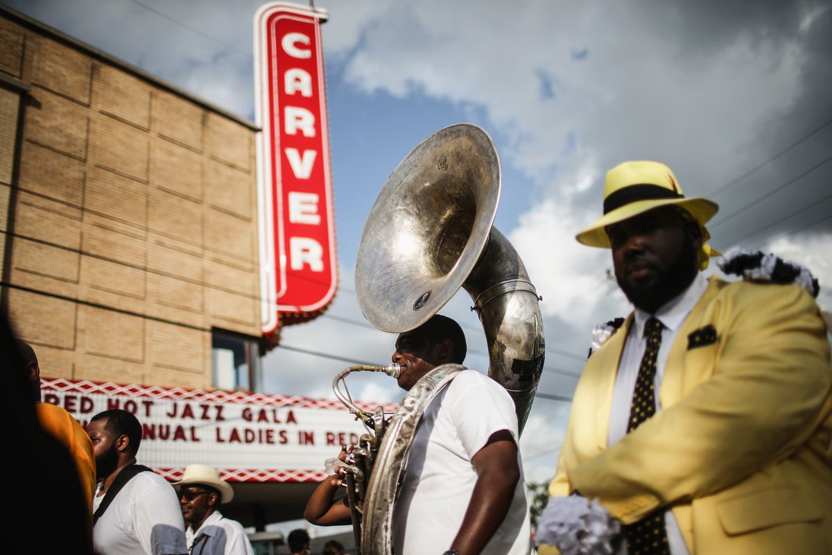 Two men stand in front of a historic theater, one wearing a sousaphone and the other in a yellow suit