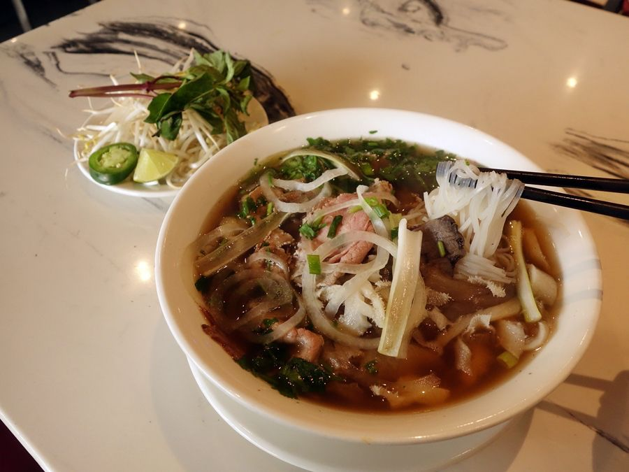 A bowl of pho at Pho So 1, next to a selection of garnishes