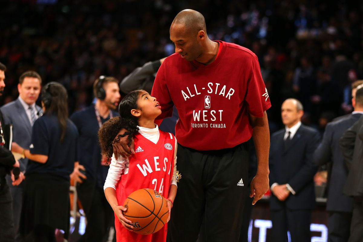Gianna Bryant, holding a basketball, looks up at Kobe Bryant, who looks down at her.