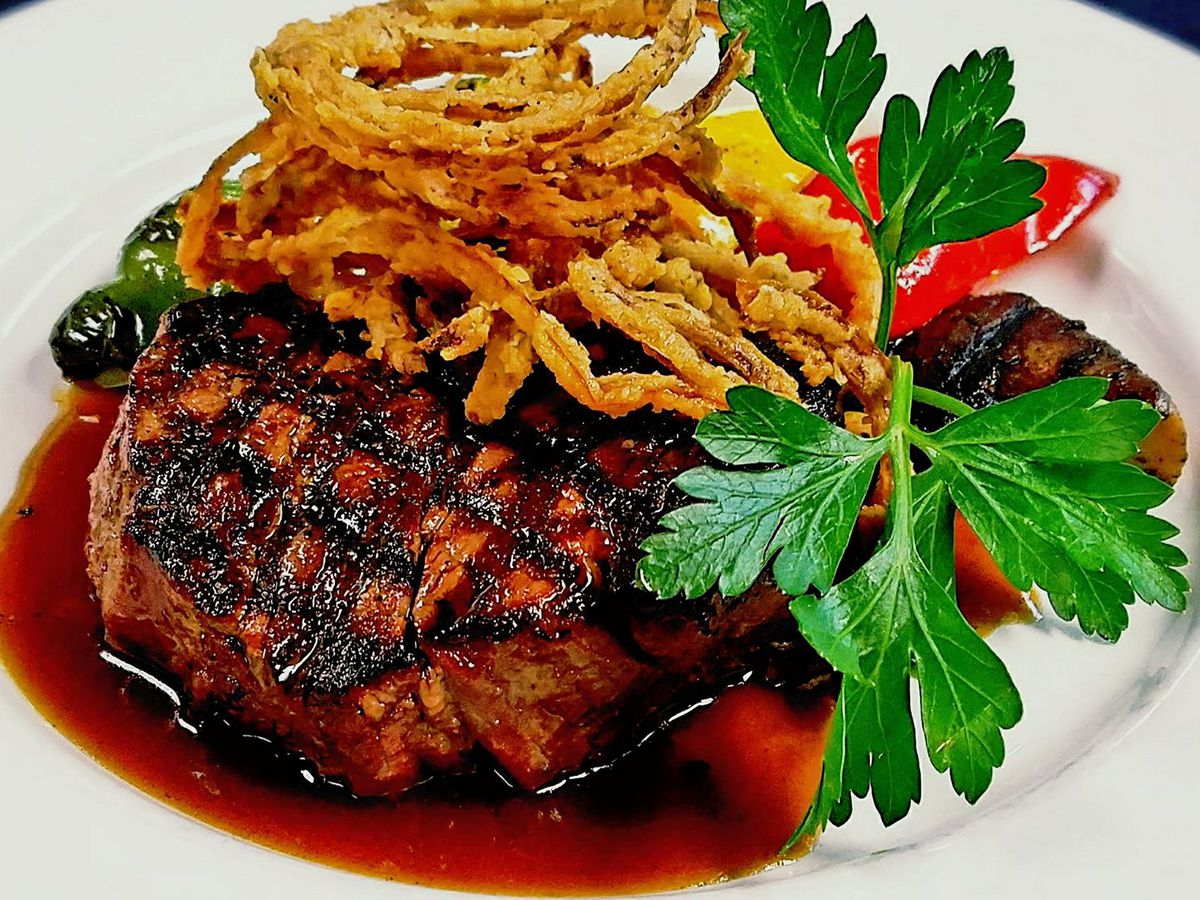 A grilled steak topped with fried crispy onions, a parsley garnish, and served over a red wine sauce