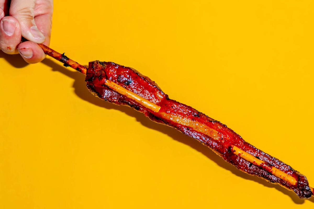 A hand holding brown-sugar pork belly on a stick against a yellow background