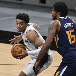San Antonio Spurs' Keldon Johnson, left, drives around Utah Jazz's Derrick Favors during the second half of an NBA basketball game, Sunday, Jan. 3, 2021, in San Antonio.
