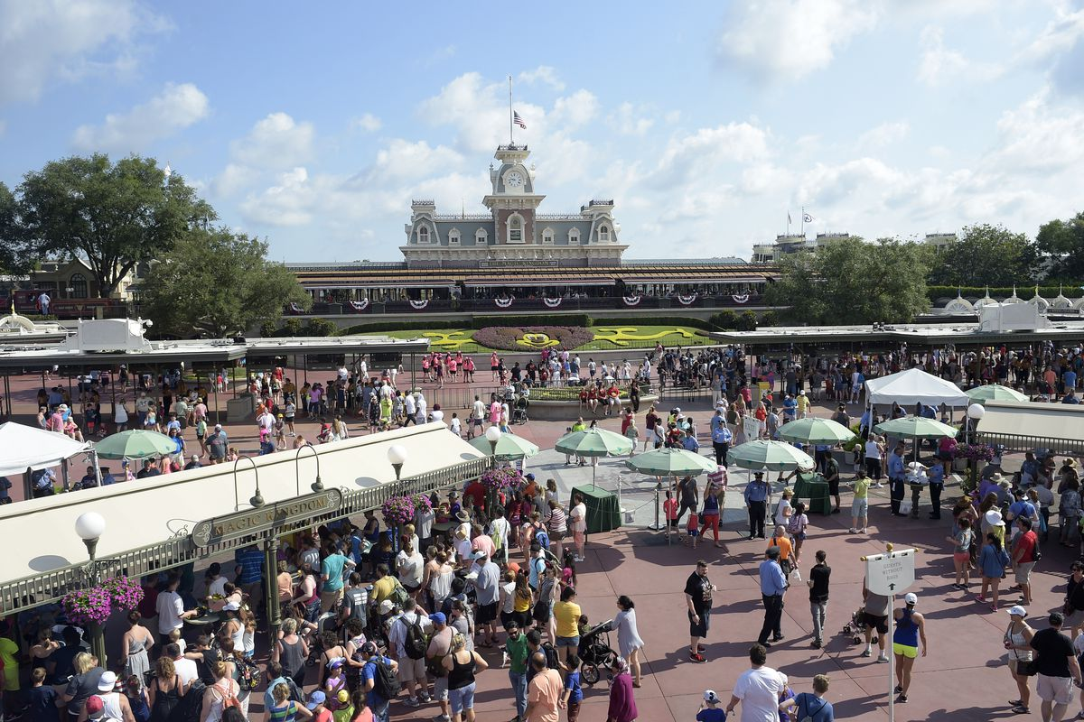 FILE - In this June 15, 2016, file photo, guests appear at the entrance to Disney's Magic Kingdom theme park in Lake Buena Vista, Fla. Disney is offering to pay full tuition for hourly workers who want to earn a college degree, finish a high school diplom