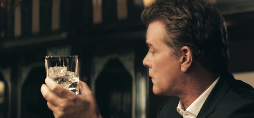 Ray Liotta holding a glass of tequila on the rocks