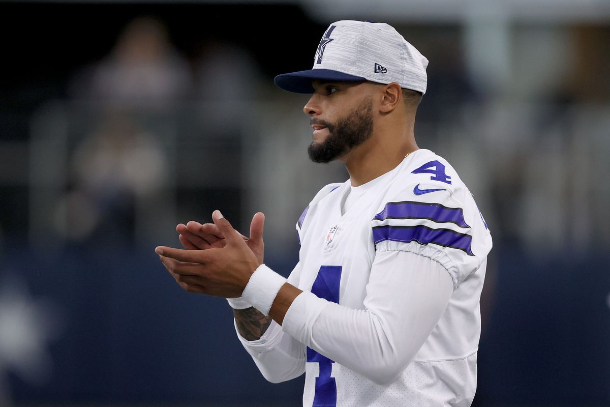 Quarterback Dak Prescott #4 of the Dallas Cowboys looks on from the sidelines as the Dallas Cowboys take on the Houston Texans in the first quarter of a preseason NFL game at AT&T Stadium on August 21, 2021 in Arlington, Texas.