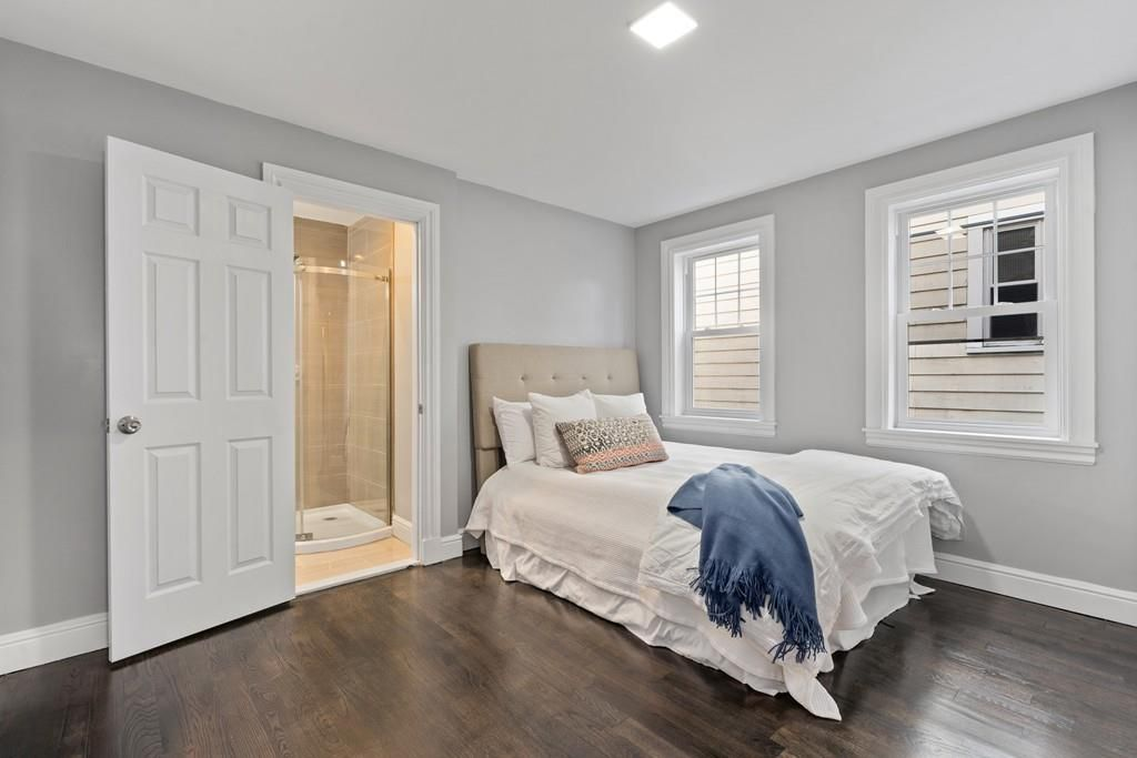 A bedroom with a bed and a door opened into a bathroom.