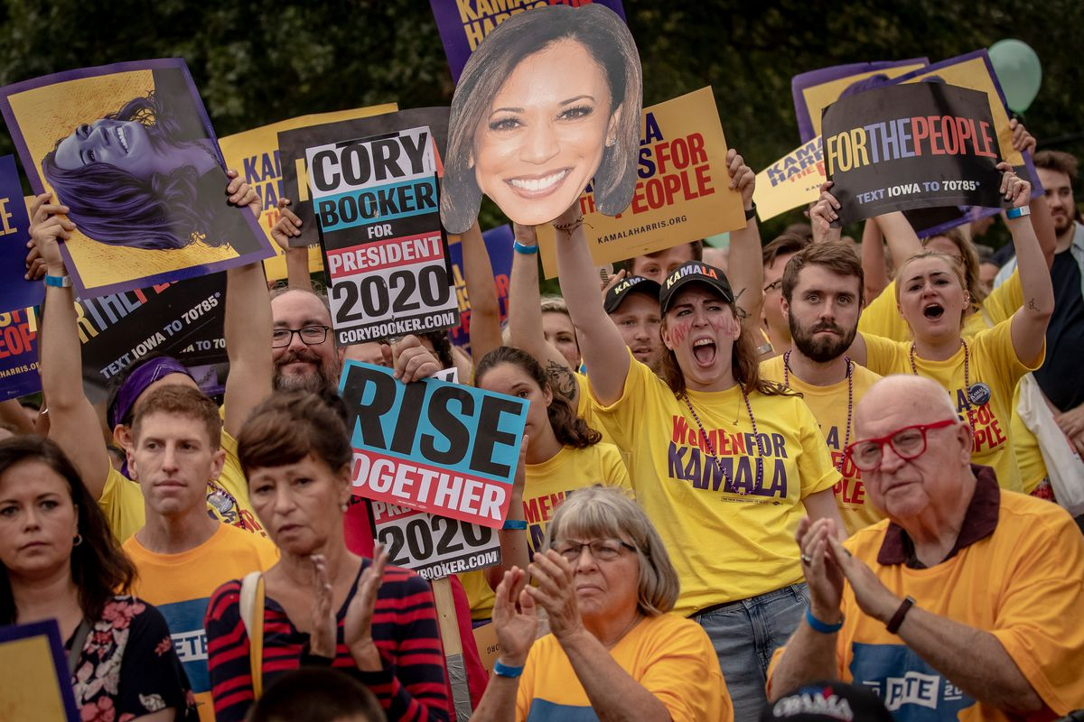 Supporters for Cory Booker and Kamala Harris cheer and hold up signs.
