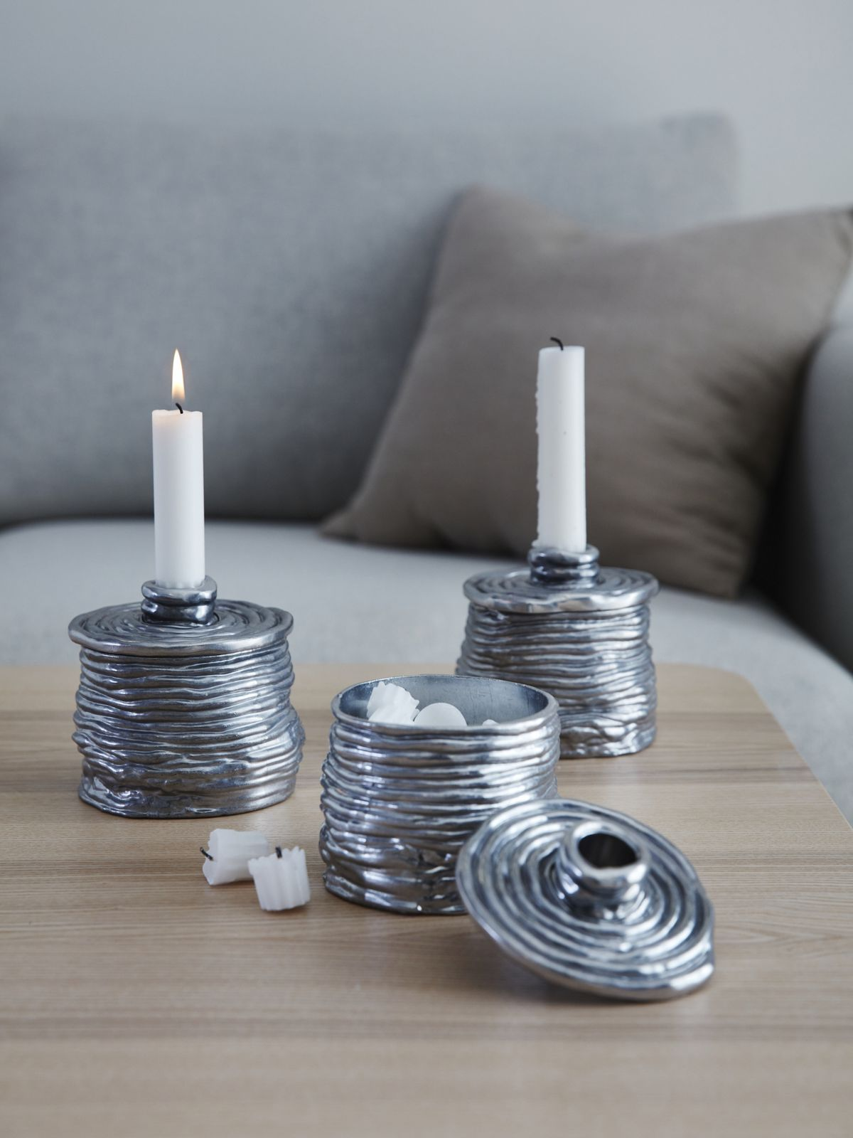 Three silver candle holders with removable lids sits on a table.