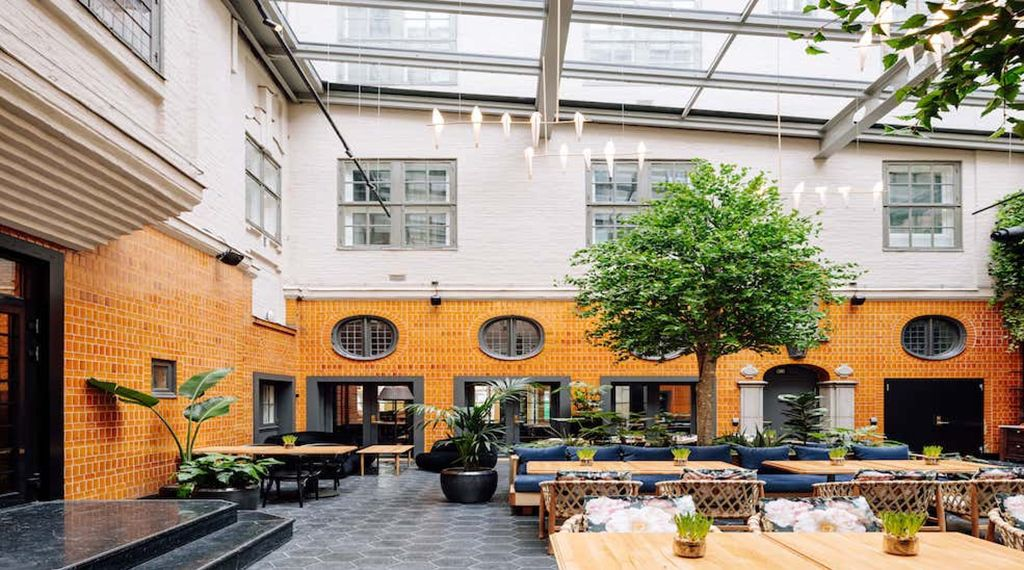 An open-air courtyard features orange-yellow wall, wooden tables set for dining, trees, and a glass ceiling.