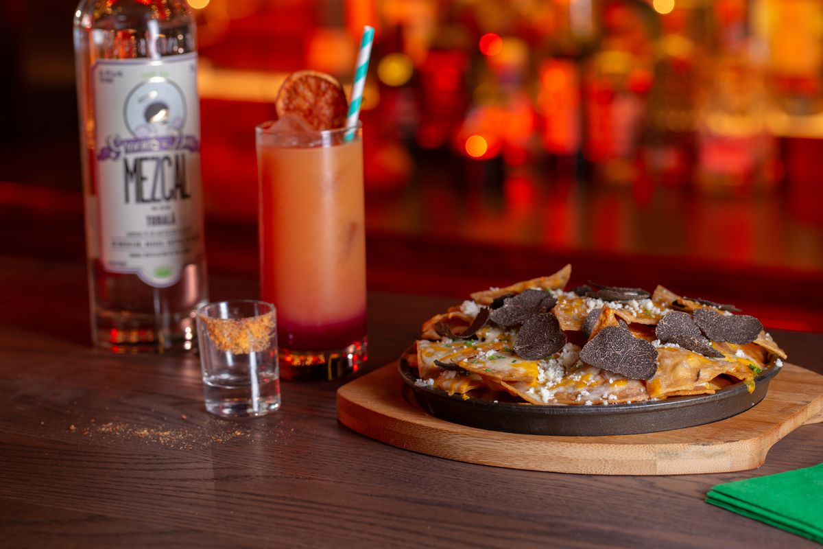 a plate of nachos with mezcal on the side